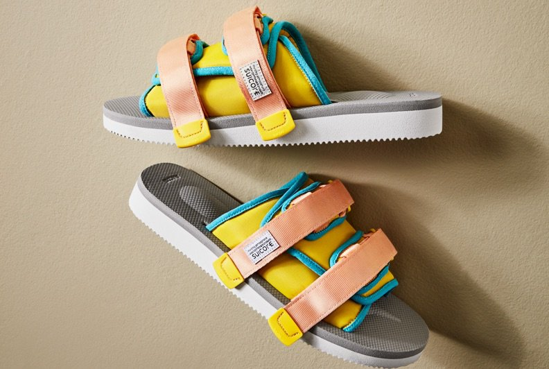 A pair of athletic sandals with yellow, green, and pinkvelcro straps and a grey and white sole.