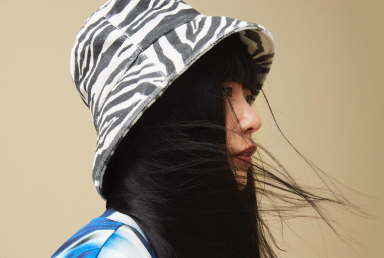 A female model in profile wearing a Zebra print bucket hat and abstract print shirt.