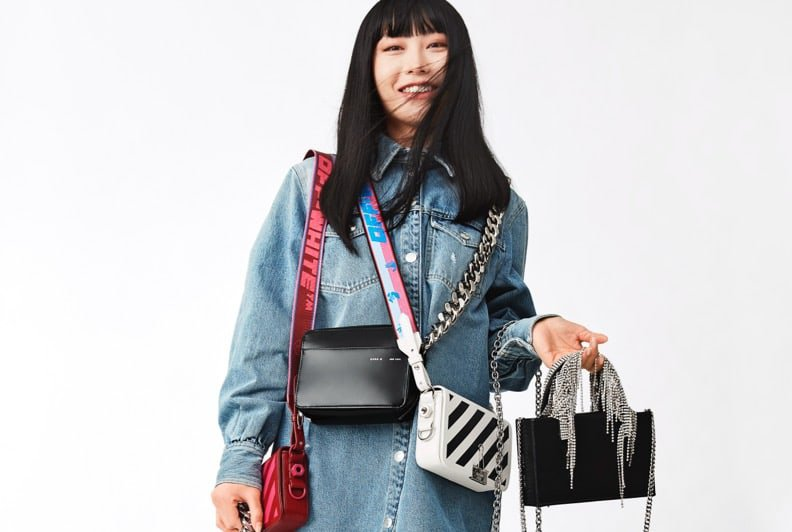 A female model in a denim shirt and jeans, wearing and holding a varety of colourful bags.