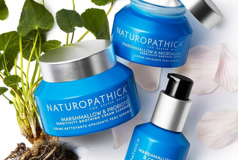 Three Naturopathica products in blue and silver packaging, with foiliage and petals in the background.