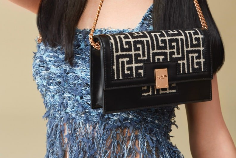 A female model wearing a blue tweed top and skirt, holding a black handbag by a gold chain.