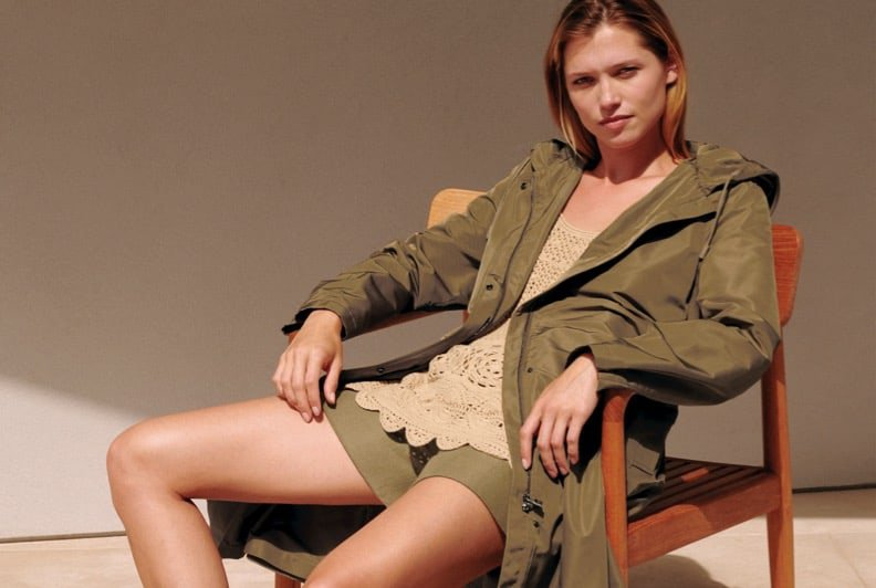 A female model sitting in a chair and wearing an olive green jacket, shorts, and a lace top.