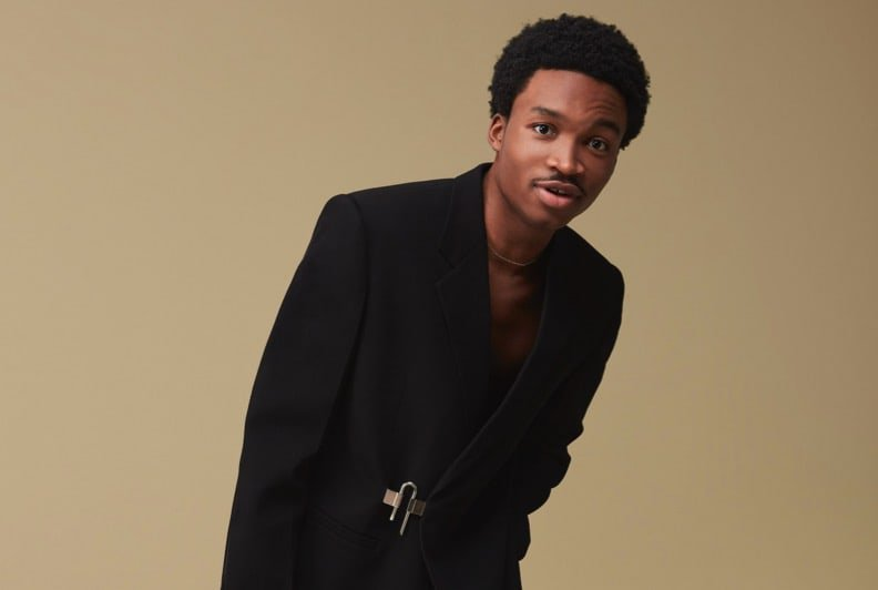 A male model wearing a black blazer with a silver buckle closure at the waist.