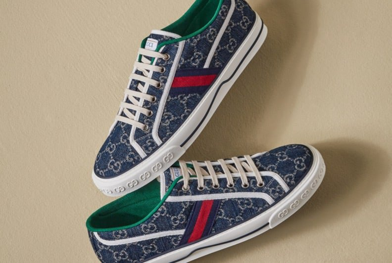 A pair of Gucci lace up sneakers in blue canvas with a white pattern and accents.