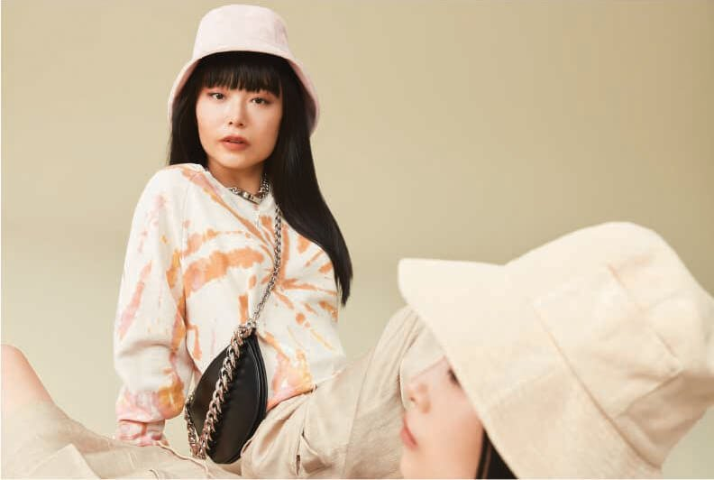 Two female models laying down wearing neutrl outfits and matching beige bucket hats.