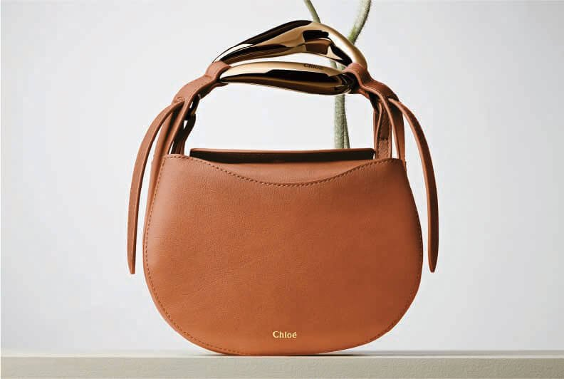 A small, round, light brown leather bag with two flowers blooming out of the top of it.