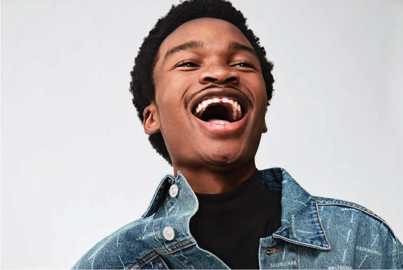 A male model wearing a black t-shirt and a denim jacket laughing.