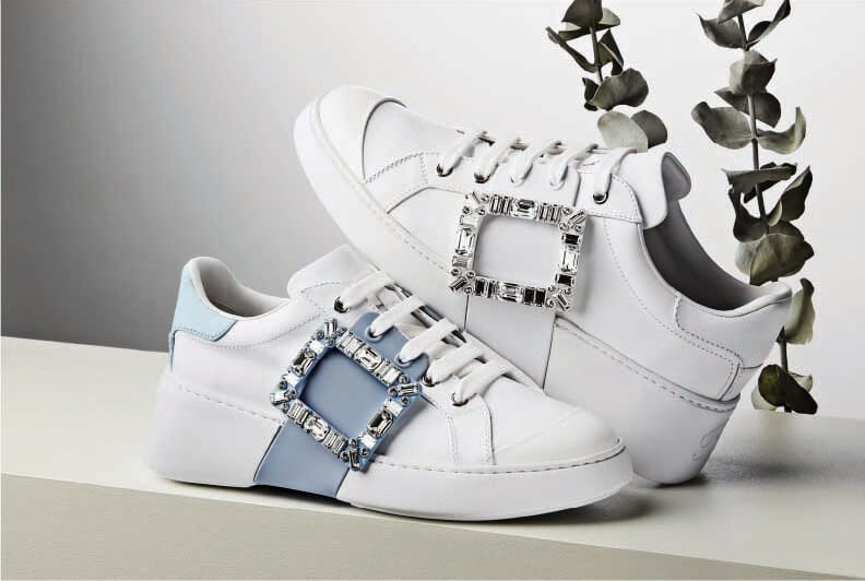 A pair of white sneakers with large crystal buckles with part of a plant visible in the background.