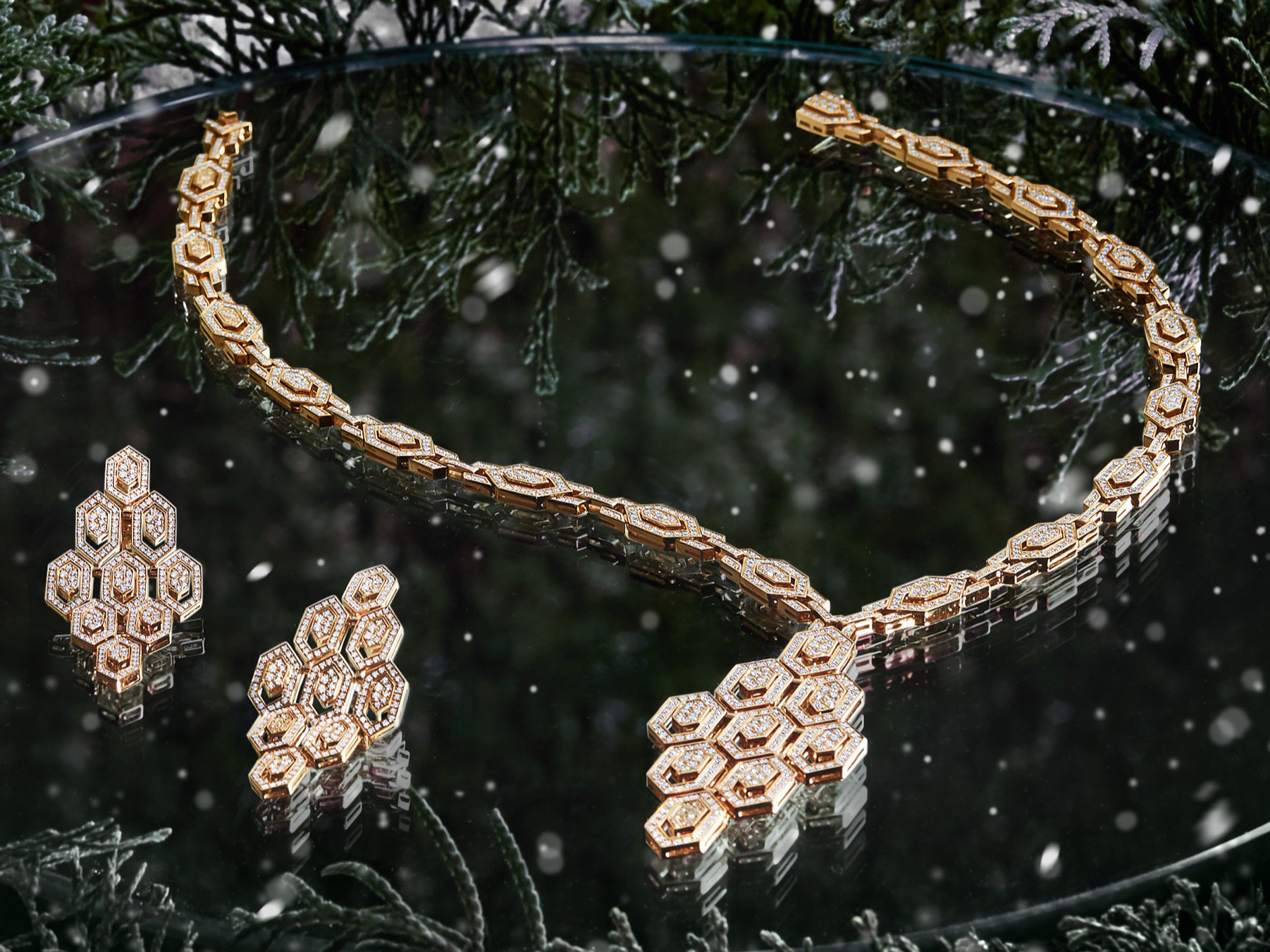 A pair of gold earrings with diamonds and a diamond necklace placed on a reflected surface surrounded by festive green foliage.