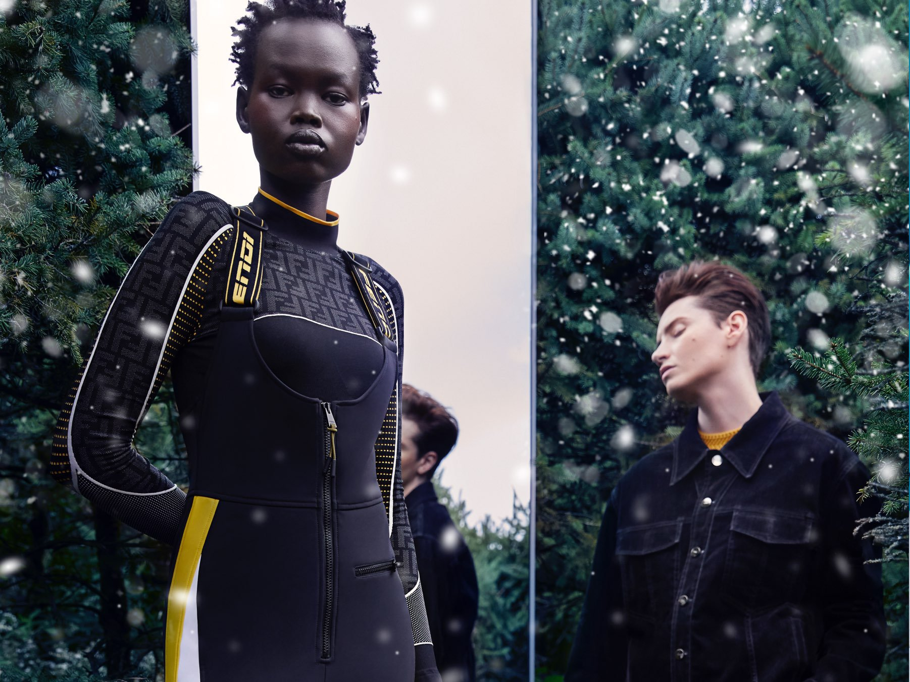 Two models standing in front of a mirror and a hedge—the female model wearing a Fendi ski jumpsuit in black and yellow, and the male model wearing a black outfit.