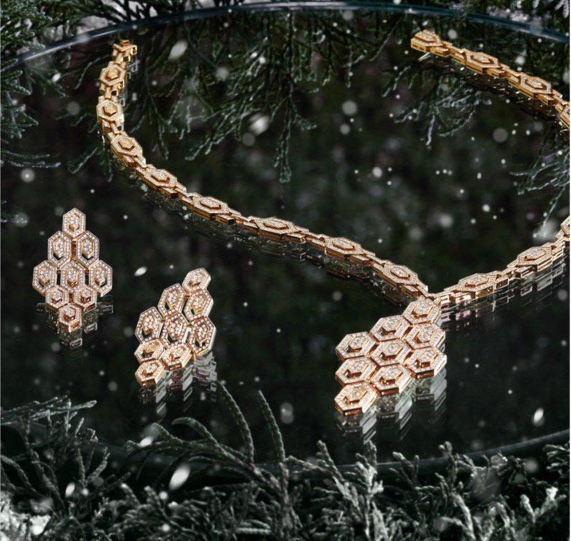 Paire de boucles d'oreilles en or avec diamants et collier de diamants, déposés sur une surface réfléchissante et entourés de feuillage vert festif.