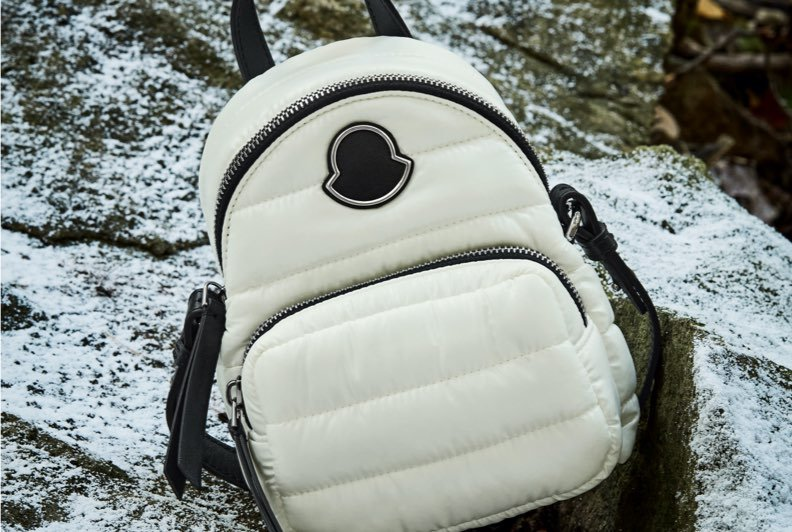 A white puffy backpack resting on snow covered rocks