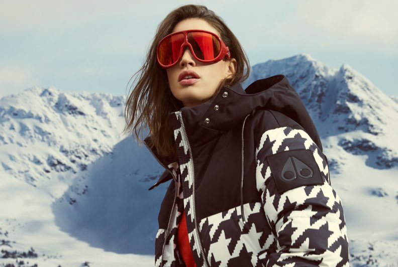 A model wearing a houndstooth printed parka and red ski goggles with a mounain in the background