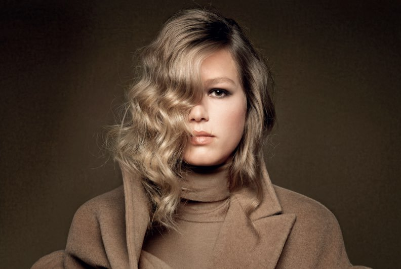 A blonde model wearing a camel coloured coat and turtleneck against a camel coloured backdrop