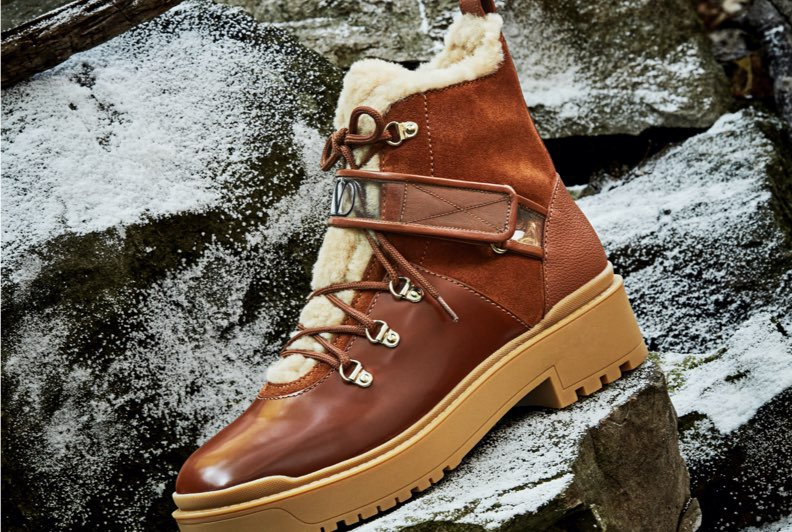 A brown, shearling lined boot wih a lug sole photographed on snow covered rocks