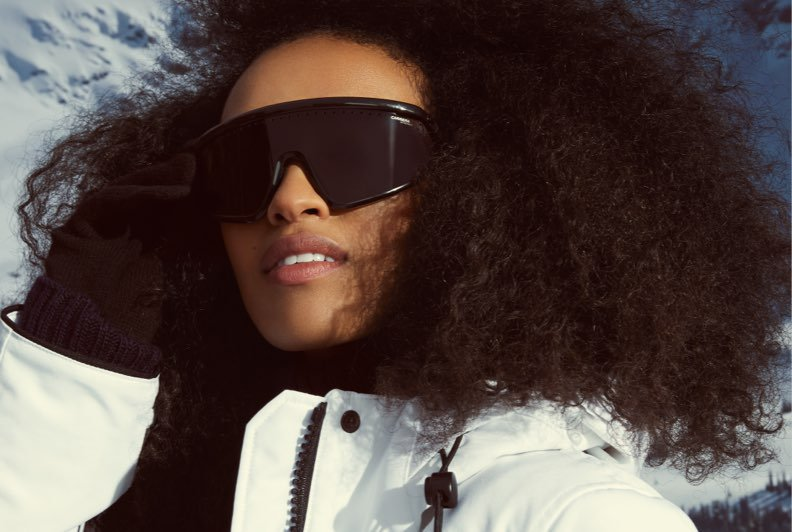 A close up shot of a female model wearing a white parka and a pair of polarized sunglasses