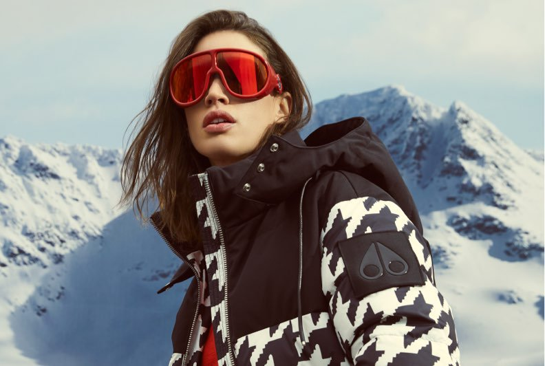 A model wearing a black and white houndstooth print parka and red goggles standing in front of a snowy mountain backdrop.