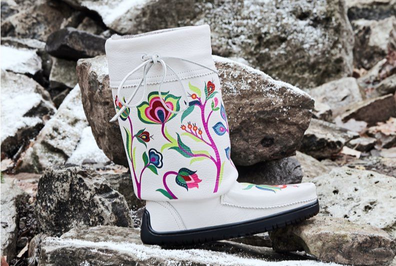 A white mukluk boot with brightly coloured beading photographed against a snowy, rocky surface