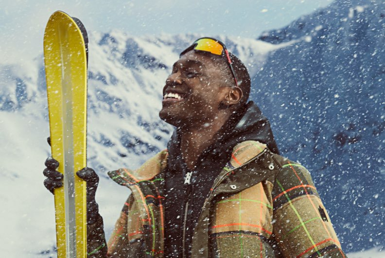 A male model in a plaid parka holding a set of skis and smiling in the snow with a mountain in the background