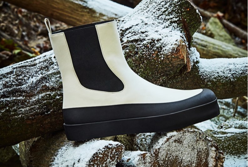 A white winter boot with black gussets and sole resting on snow covered wood