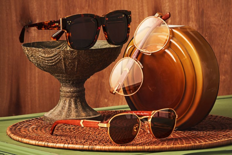 Two pairs of sunglasses and one pair of optical glasses styled on top of a green side table