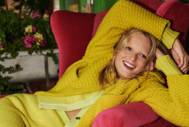 A model wearing a bright yellow knit outfit reclining on a red velvet wingback chair