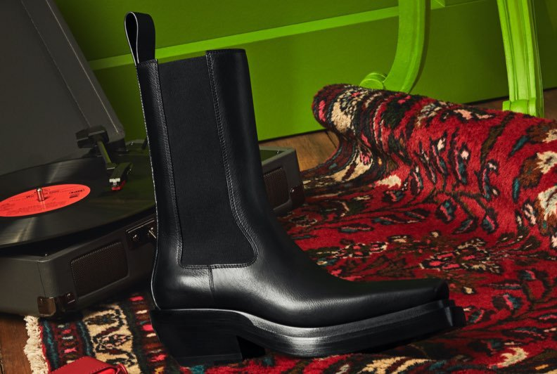 A brown leather ankle boot with a gussets on the side resting on a patterned carpet against a bright green background