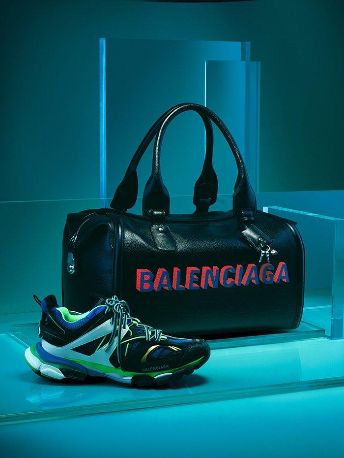 Holt Renfrew Image of GIVENCHY sneaker de sport en bleu, orange et vert. 1 205 $ la paire. Grand sac de sport en cuir noir à logo Balenciaga. 4 190 $.