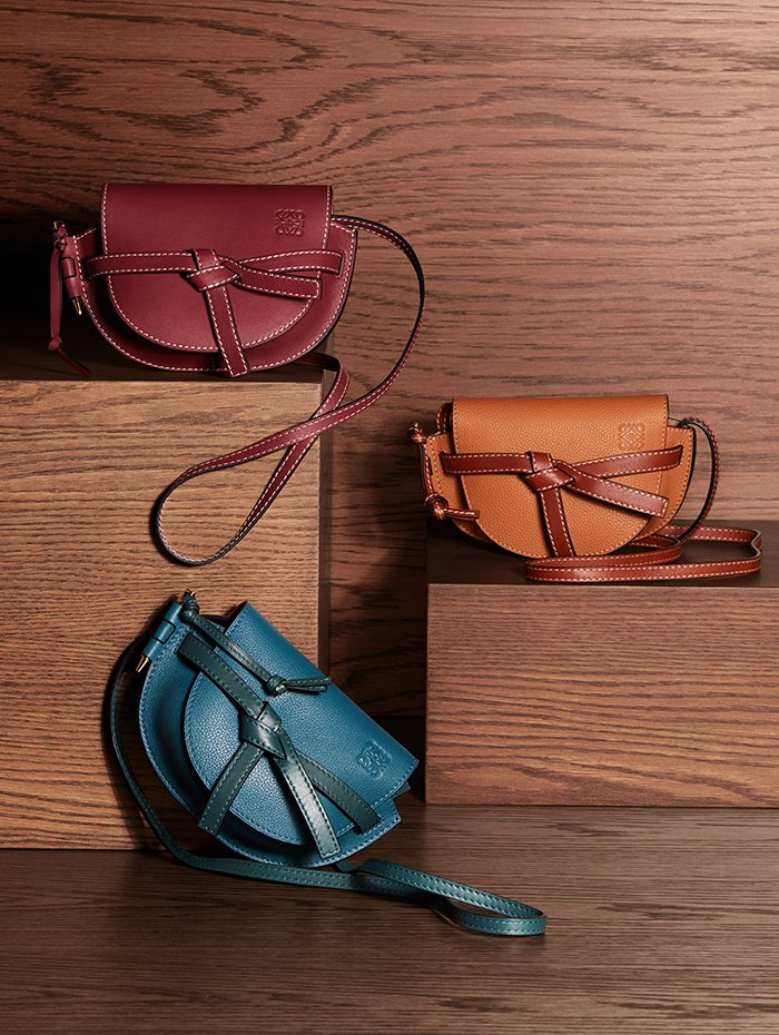 Holt Renfrew Image of LOEWE smooth leather Gate Mini crossbody in wine. $1590. Grained leather Gate Mini crossbody in petroleum blue and Cypress, or light caramel and pecan. $1550 each.