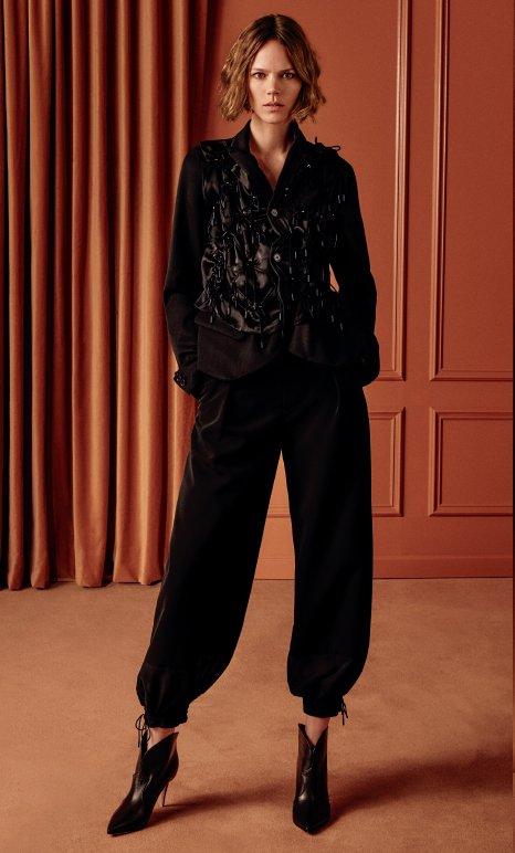 Holt Renfrew image of NOIR KEI NINOMIYA Long sleeve jacket with ruche tie embellishment. $2115. Grosgrain jogger. $730. Both in black. SHOP NOW