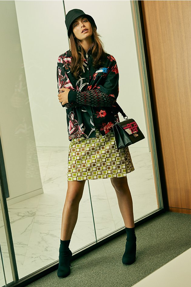 Holt Renfrew image of PRADA cotton poplin shirt in rose print. $1240. Wool and cashmere sweater in chevron pattern. $1340. Cotton poplin skirt in checkered print. $1130. Nylon bucket hat. $395. Elektra leather bag. $3550. Heeled sock boot with logo in black. $1155. SHOP NOW