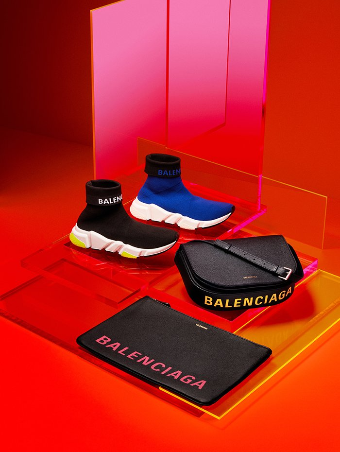 Holt Renfrew image of Balenciaga Fabric Speed sneaker with logo. $1065 each. Ville pouch in noir and rose. $1035. Ville messenger bag with flap in bleu tempette and jaune. $2065. Both in leather with logo.