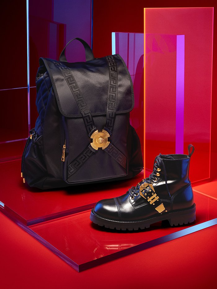 Holt Renfrew Image of VERSACE silk backpack with harness buckle. $3200. Leather boot with strap buckle. $2150. Both in black.