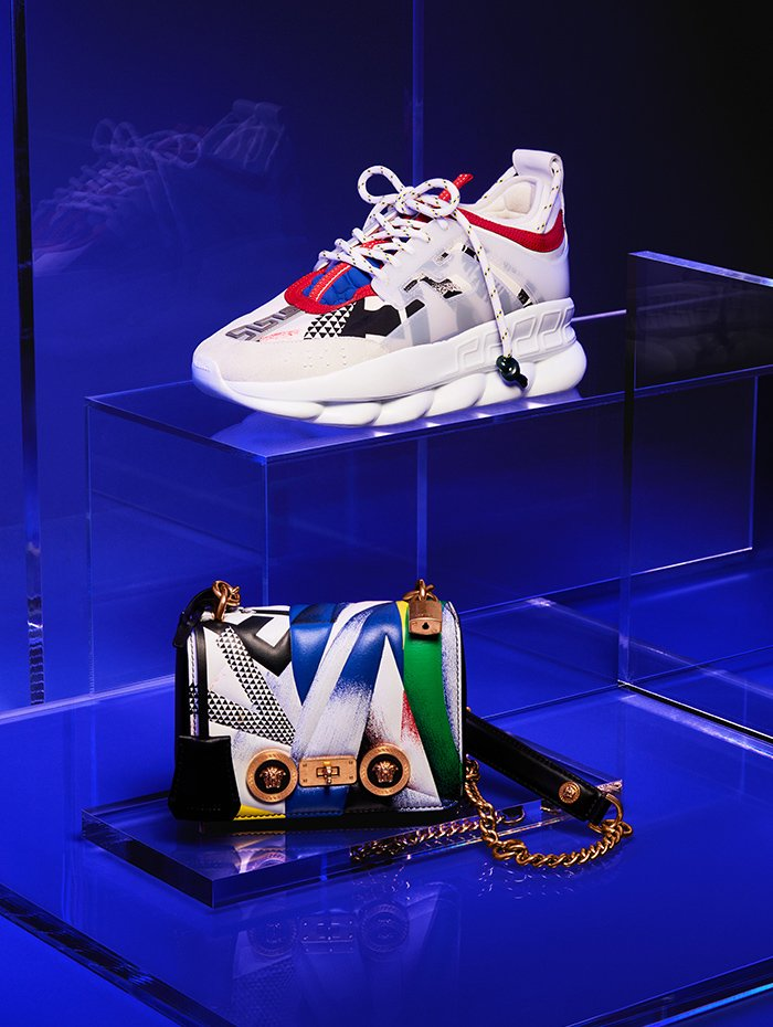 Holt Renfrew image of Versace Leather Chain Reaction sneaker. $1225. Leather Icon mini shoulder bag in Clash print. $2700.