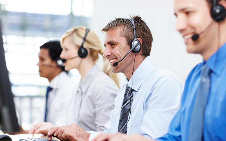 Friendly representative smiling while assisting someone over the phone, with colleagues on either side - copyspace