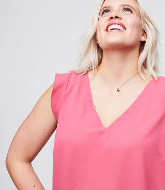 Engineered with stretch-effect fabric for maximum comfort and movement, flutter sleeves are a femme finish for this oh-so-polished and fluid shell. V-neck. Flutter cap sleeves. Shirred beneath back yoke. Shirttail hem.