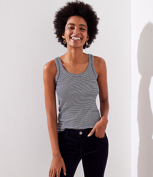 In super soft cotton, this flattering scoop neck tank is our go-to layer. Scoop neck. Sleeveless. Banded trim with tonal topstitching at neckline and armholes. Shirttail hem.