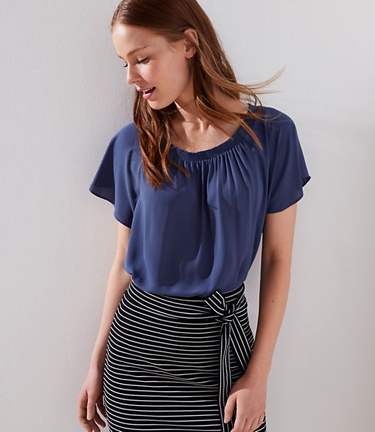 Woven at front and knit at back, this flowy top is styled with a smocked neckline for a fresh touch of texture. Round neck. Short raglan sleeves.
