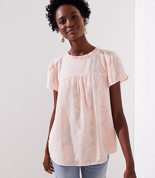 In the softest tonal rose jacquard, this soft top is femme, flirty, and flowy. Ruffled round neck. Flared short sleeves. Back button keyhole. Shirttail hem.