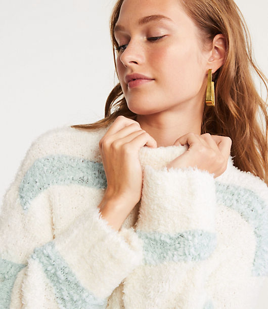 Irresistibly fuzzy - and starring textured stripes - this powder soft plush knit is the ultimate to cuddle up with. Mock neck. Long sleeves. Side slits. Hi-lo hem.