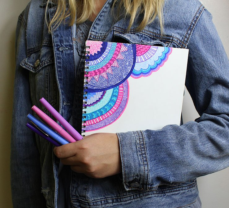 girl-holding-hand-doodled-cover-of-notebook-with-papermate-flair-pens.jpg