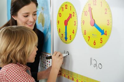 student-learning-how-to-tell-time-writing-time-in-expo-marker-beneath-clock.jpg