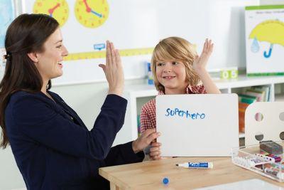 teacher-high-fiving-student-holding-expo-whiteboard-with-superhero-written-in-blue-expo-marker.jpg