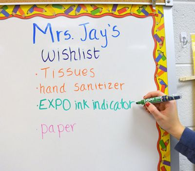 teacher-writing-on-decorated-board-with-green-ink-indicator-marker_bp3p.jpg