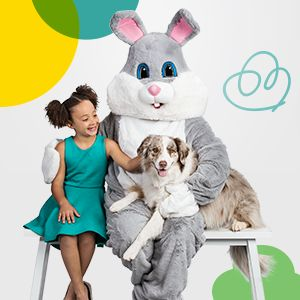 Photo of the Easter Bunny with a little girl dressed up on one leg, and a dog lying on his other leg.