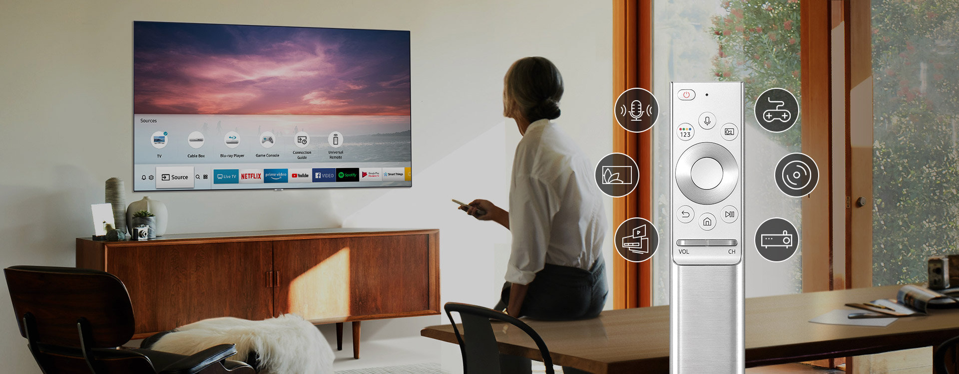 In front of the TV is a woman sitting on the desk with a remote. Next to her is an image of an enlarged remote with 6 icons. The icons represent that remote controls for several devices such as game and DVD players are integrated into one remote control.