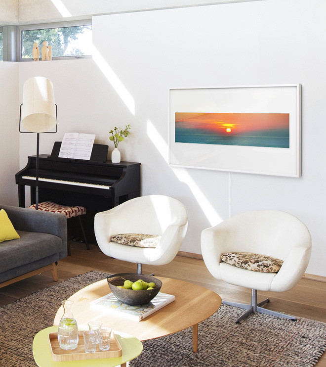 The Frame on the wall displaying a photograph of a sunset in a Panoramic layout with Polar White matte color in a living room with arm chairs. Next to the Frame is a piano.