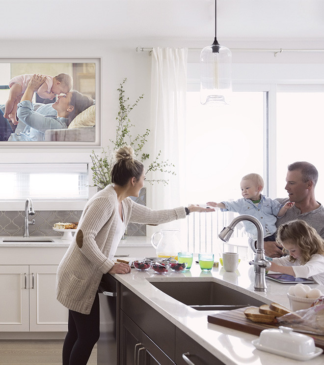The Frame is mounted on a wall in kitchen, displaying a family portrait in Shadow Box layout with Polar White matte color.