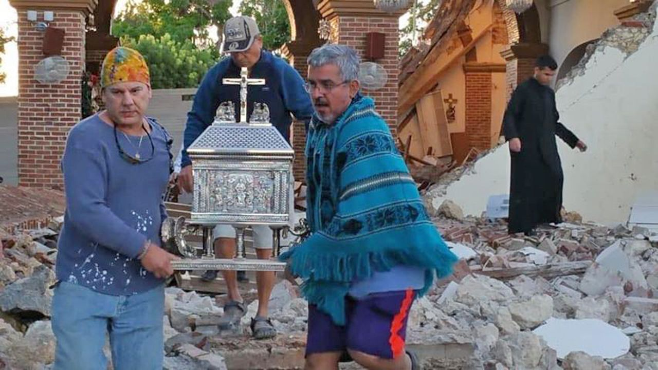 Damage, like that of the Guayanilla Catholic Church, can be seen in the town of Guayanilla after a powerful earthquake struck Puerto Rico on Tuesday, January 7, 2020. People are seen taking a religious relic out of the damage church. (Photo courtesy of the family and friends of Belisa Rivera Negron)
