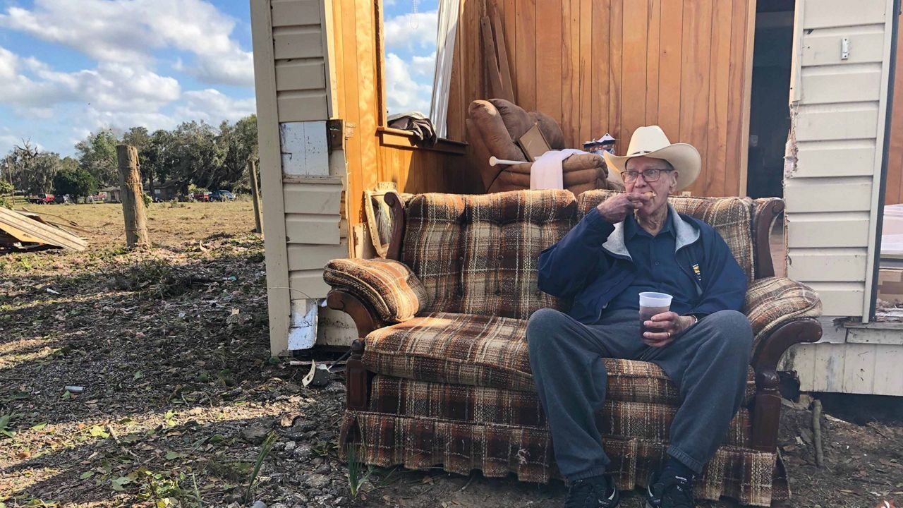 Eighty-five-year-old Jim Madison sits on his couch outside the shell of the house he called home for 58 years. (Tony Rojek/Spectrum News 13)